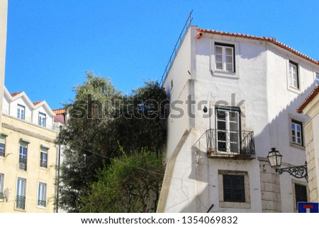 Old colorful and beautiful facades with vintage streetlight in Lisbon streets in Spring. Clothesline in the facade with hanging clothes #1354069832