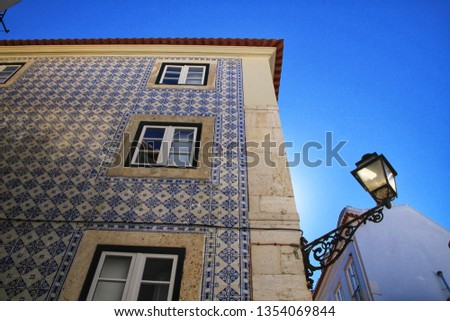 Old colorful and beautiful facades with vintage streetlight in Lisbon streets in Spring. Clothesline in the facade with hanging clothes #1354069844
