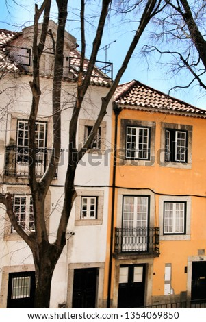 Old colorful and beautiful facades with vintage streetlight in Lisbon streets in Spring. Clothesline in the facade with hanging clothes #1354069850