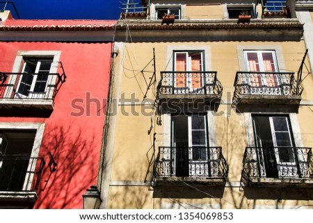 Old colorful and beautiful facades with vintage streetlight in Lisbon streets in Spring. Clothesline in the facade with hanging clothes #1354069853