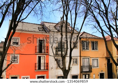 Old colorful and beautiful facades with vintage streetlight in Lisbon streets in Spring. Clothesline in the facade with hanging clothes #1354069859