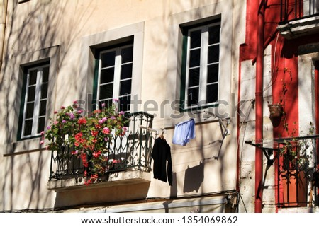 Old colorful and beautiful facades with vintage streetlight in Lisbon streets in Spring. Clothesline in the facade with hanging clothes #1354069862