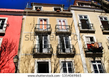 Old colorful and beautiful facades with vintage streetlight in Lisbon streets in Spring. Clothesline in the facade with hanging clothes #1354069865