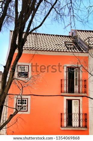 Old colorful and beautiful facades with vintage streetlight in Lisbon streets in Spring. Clothesline in the facade with hanging clothes #1354069868