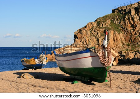 Old colorful fishing boats moored on the beach (Blanes - Costa Brava, Spain) - stock photo
