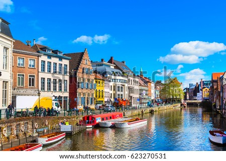 old colorful traditional houses along the canal and boats in popular touristic destination Ghent, Belgium #623270531