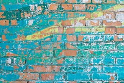Old colorful (turquoise and yellow) paint with cracks on red brick wall as background, texture