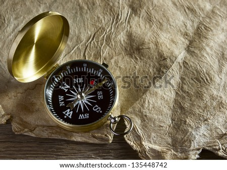Old compass and paper on wooden background