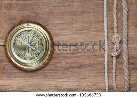 Old compass and rope frame on wooden background