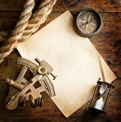 Old compass, astrolabe and rope on vintage paper. Adventure stories background.