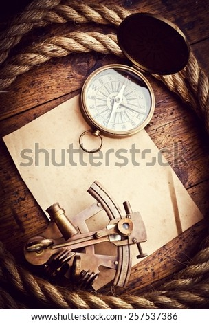 Old compass, astrolabe and rope on vintage paper. Adventure stories background. #257537386
