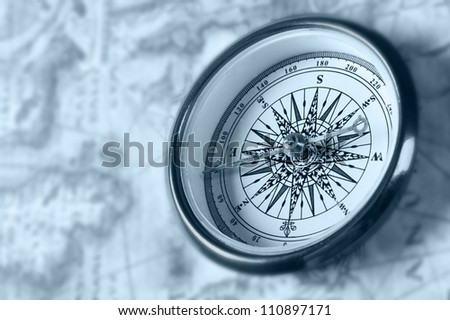 Old compass on ancient map. Blue toned image