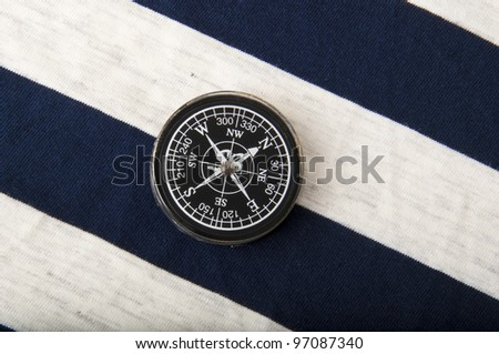 Old compass on the background of a sailor dress - stock photo