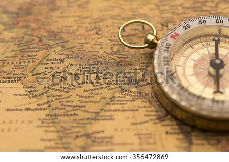 Old compass on vintage map selective focus on India