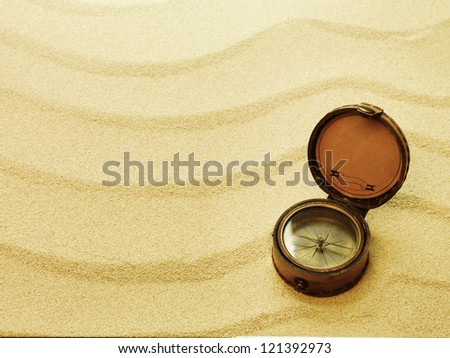 old compass with sand as background
