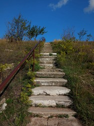 Old concrete stairs with rusty iron pipe handle leading to the blue sky. High hill with trees and green grass. Beautiful landsaft. Rural style.