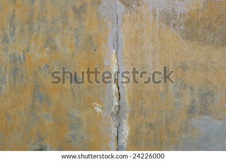 Old concrete wall with yellow cracked grout