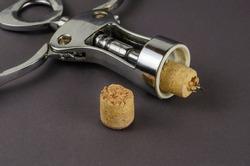 Old corkscrew and broken cork on a gray background. The corkscrew lies next to a broken wine cork. Selective focus