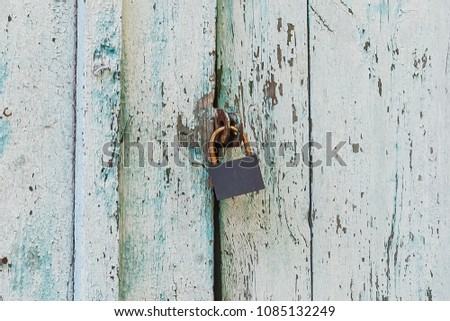 Old corroded padlocked on the wooden door. Vertical wooden planks texture.
