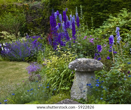 old cottage garden with delphinium and stone mushroom shaped garden ornaments