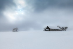 Old cottage in winter in the mountains
