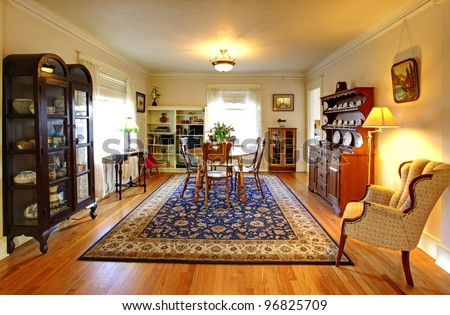 Old country English charm living and dining room with blue rug.