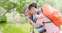 old couple smile happily and go travel in the prark