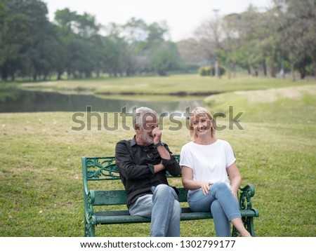 Old couple talk in a park on a sunny day. Happy senior couple relax in the forest spring summer time. free time, lifestyle retirement grandparents concept
