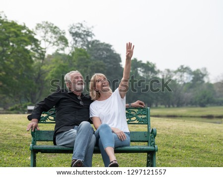 Old couple talk in a park on a sunny day sea looking and pointing to a clear horizon. Happy senior couple relax in the forest spring summer time. free time, lifestyle retirement grandparents concept