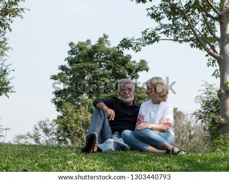 Old couple talk in a park on a sunny day. Senior couple relax in the forest spring summer time. free time, lifestyle retirement grandparents concept.