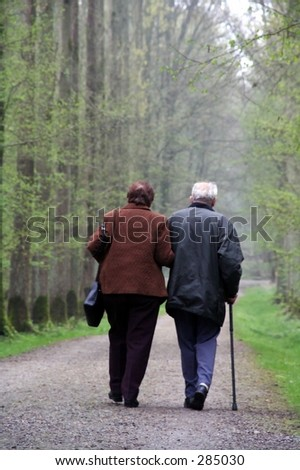 old couple walking in a forest