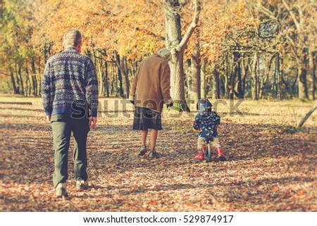 Stock Photo Old couple with grandson on a bicycle enjoying a family walk on a path with golden leaves in an autumn park