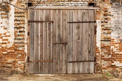 Old cowshed. Large wooden gate and dried wood. Old brick building.