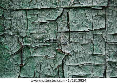 Old cracked paint pattern on rusty background. Peeling paint. Pattern of light-green grunge material. Damaged paint. Scratched old plate