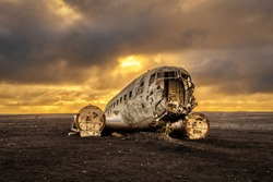 Old crashed plane abandoned on Solheimasandur beach near Vik in Iceland with heavy storm clouds in the sky. Hdr processed