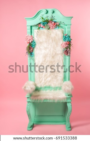Old creative cyan throne on a pink background. Front view.