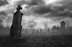 Old creepy graveyard on stormy winter day in black and white.
