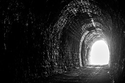 Old creepy underground stone tunnel. Halloween Locations. Dark stone tunnel illuminated by a beam of light. A light in the end of a tunnel