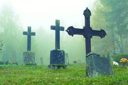 Old crosses on the graves in a cemetery in the autumn morning fog - village Ergeme in Valka municipality, Latvia