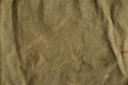 Old, crumpled and dirty khaki color tarpaulin, detailed texture. Fabric of a vintage army military or travel backpack for background. Worn natural sail cloth material with stains