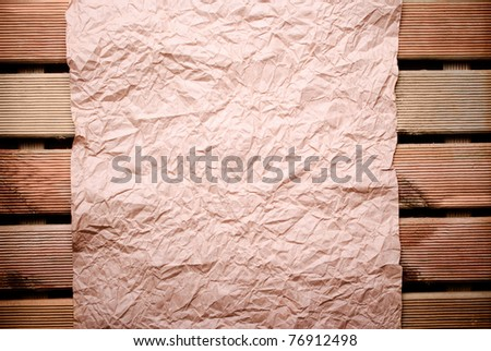 Old crumpled paper on wooden wall