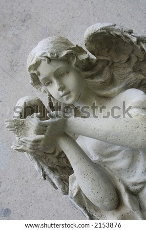 old cute angel sculpture over a gray wall