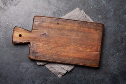Old cutting board over towel on stone kitchen table. Top view flat lay with copy space