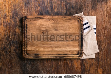 Old Cutting Board with cloth napkin on a old wooden table, top view Сток-фото ©
