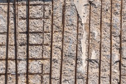 old damaged and weathered concrete wall with rusty iron rods