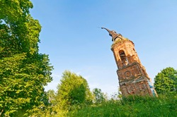 Old damaged belfry of St. Barbara Church (1700) among trees against blue sky background. Matchino village, Kaluzhsky region, Russia
