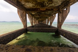 Old damaged cement bridge in the sea.
