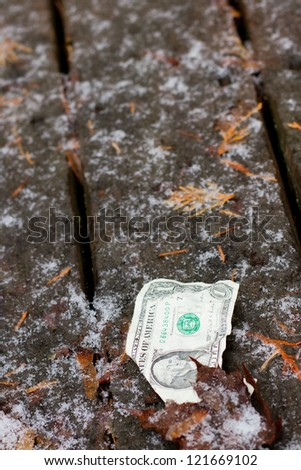 old damaged dollar bill left behind in a cold winter background
