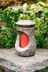 Old damaged grave lantern on a gravestone