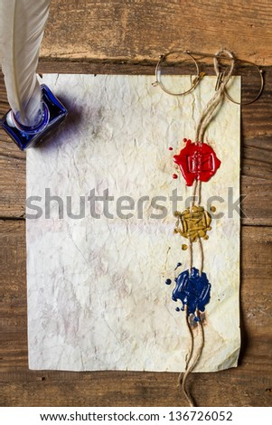 Old damaged sheet of paper with inkwells and three sealing wax